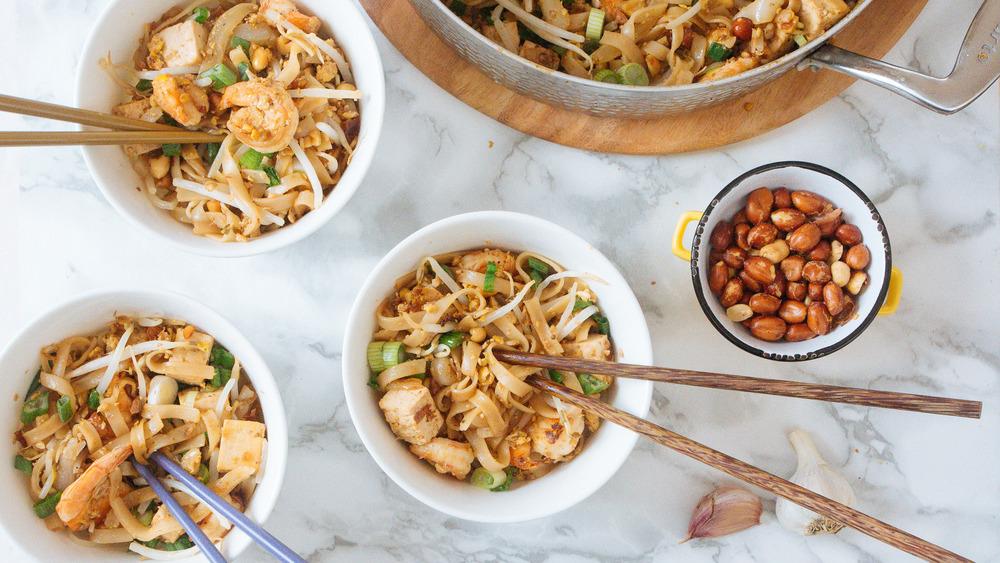 three bowls and big pan of pad thai