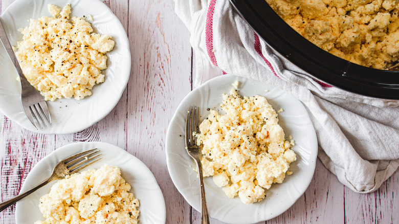 three plates of scrambled eggs