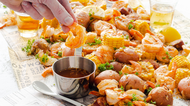 Close up of Instant Pot Shrimp Boil and a hand dipping shrimp in seasoned butter