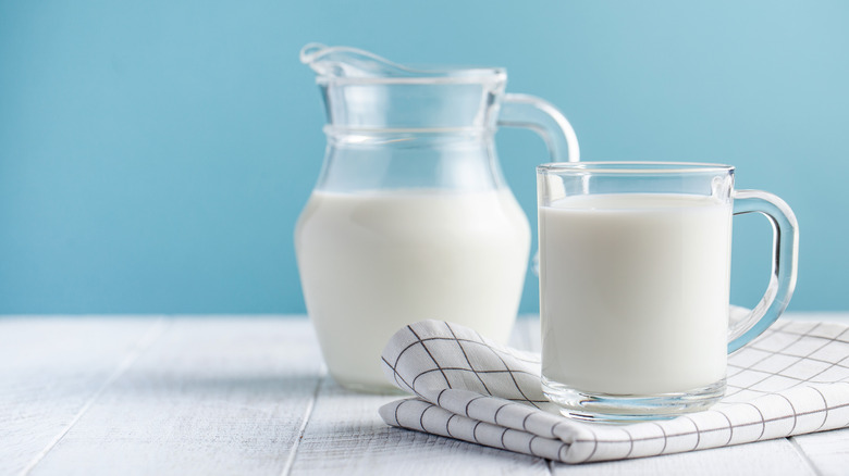 Jar and glass of cream with blue background