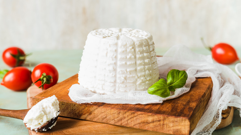 ricotta cheese on a wood board with tomatoes