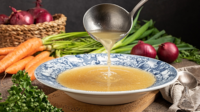 A ladle pouring vegetable broth in a bowl