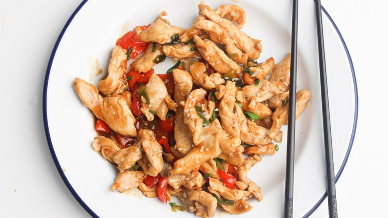 Cashew chicken on plate with chopsticks