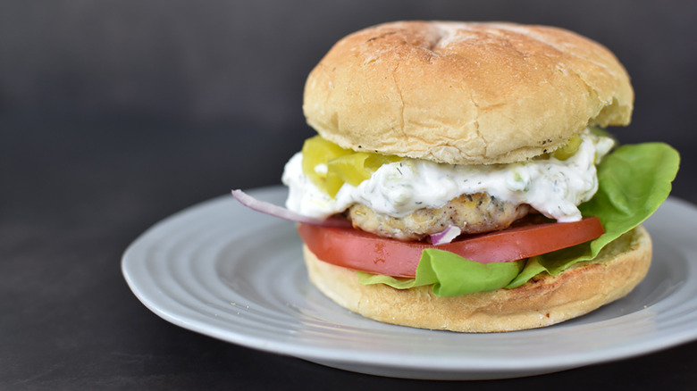 A chicken burger with lettuce, tomatoes, tzatziki sauce, red onions, and pickled banana peppers on a bun on a white plate