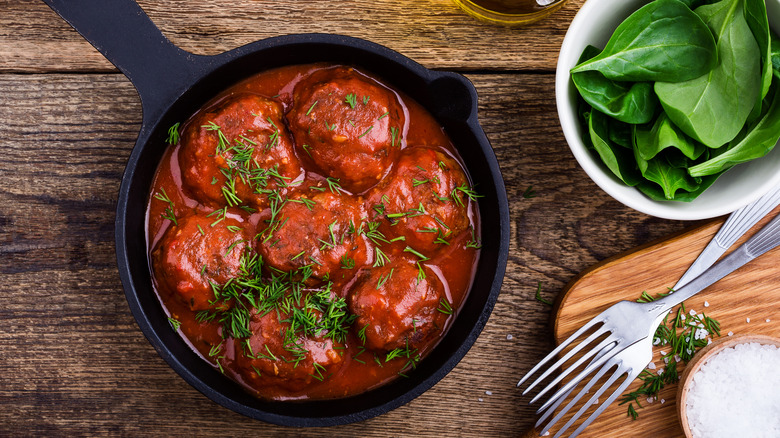 Meatballs and tomato sauce in a cast iron skillet