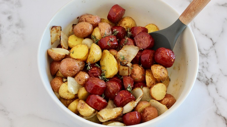 White serving bowl filled with cooked sausage and potatoes