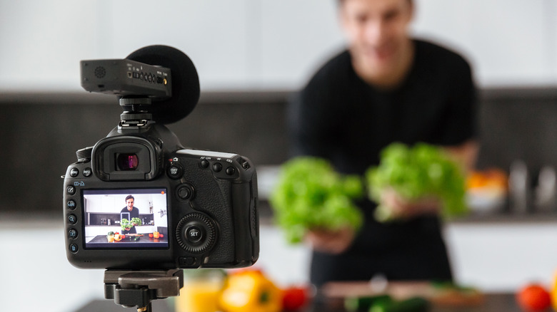 A representational image of a chef filming a video