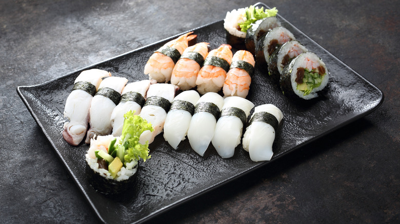Butterfish nigiri, shrimp, and maki rolls on black plate