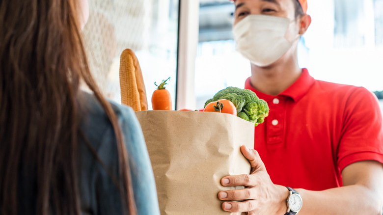 Grocery store employee handing customer bag of groceries