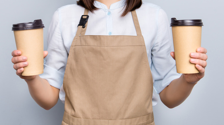 Woman barista holding two to-go cups of coffee