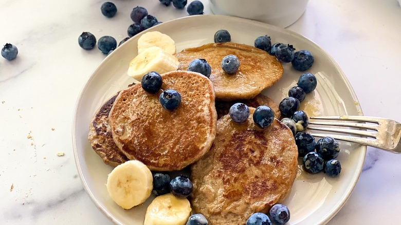 Pancakes, blueberries, and banana slices sitting on a plate