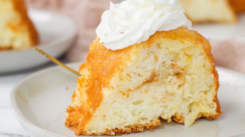 Close up of a slice of angel food cake topped with whipped cream