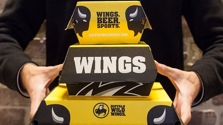 Person holding take out boxes from BWW