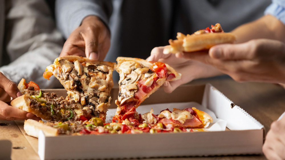 People grabbing different pizza slices