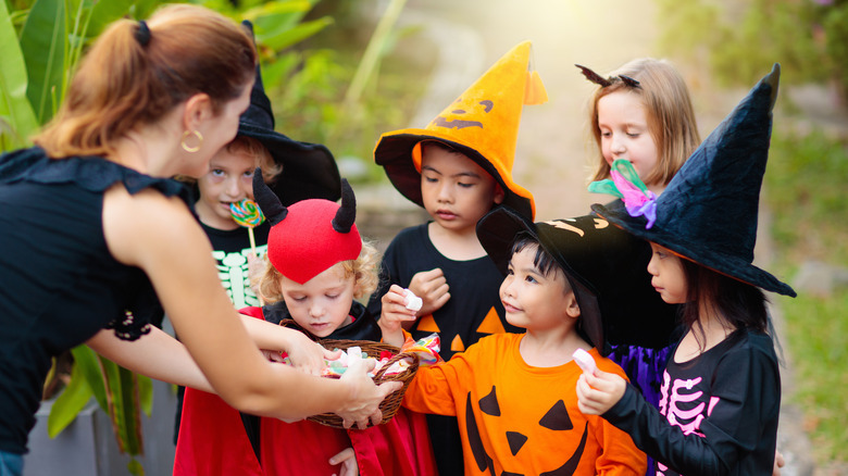 Unimpressed trick-or-treaters getting candy