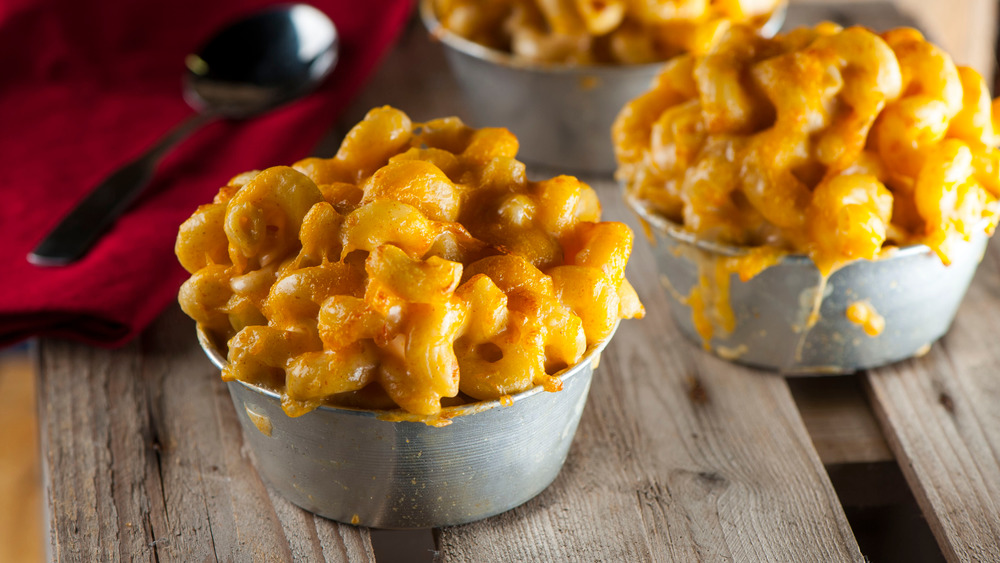 mac and cheese in small metal bowls on wood surface