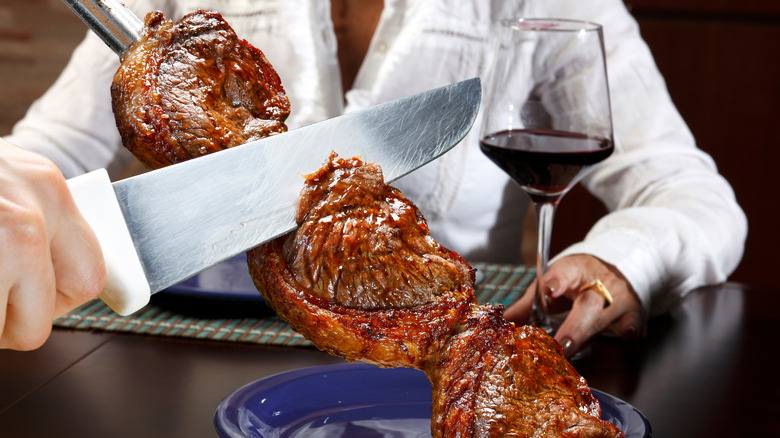A knife carving meat at a Brazilian Steakhouse