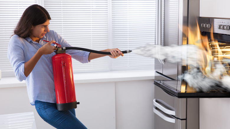 Woman using kitchen fire extinguisher