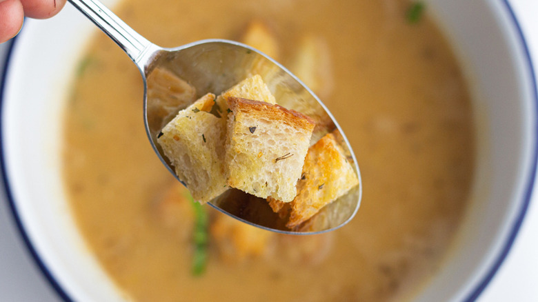 Air fryer croutons on soon above bowl of soup