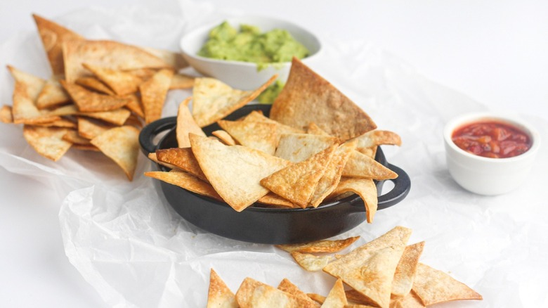 Air fryer tortilla chips with salsa and guacamole in separate bowls