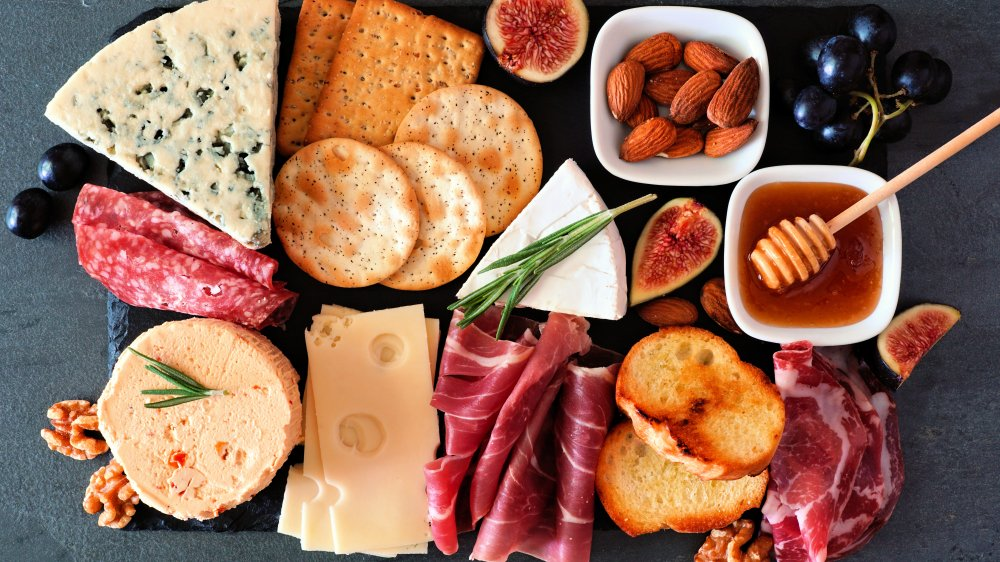 charcuterie board with cheeses, meats, almonds, fruit, and honey