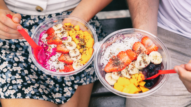 Two people eating açaí bowls