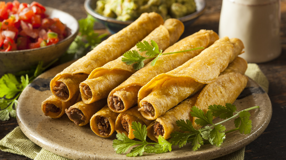 Beef taquitos stacked on plate