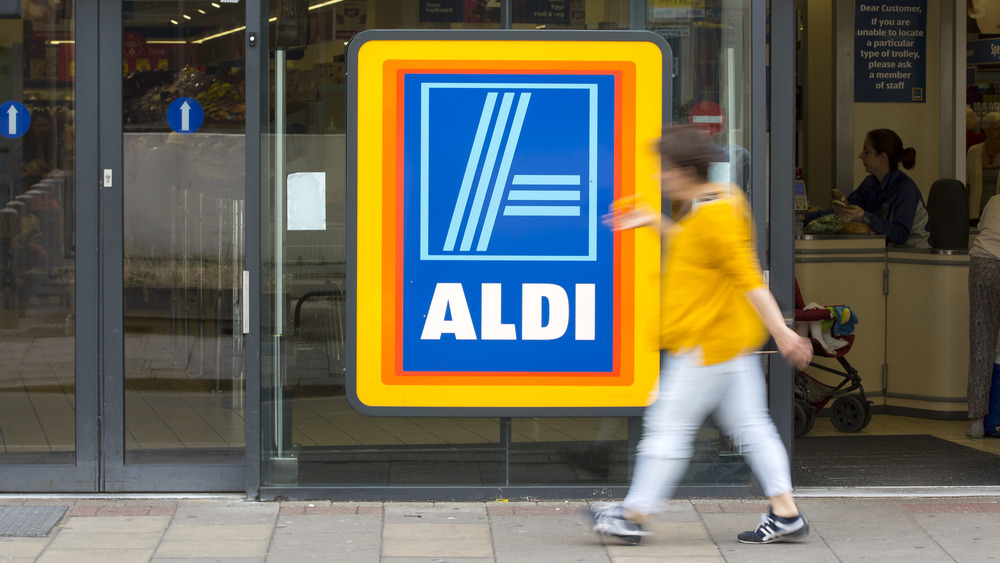 Aldi sign with person in front of it