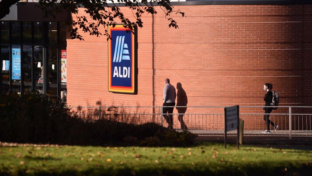 Two people walking into Aldi