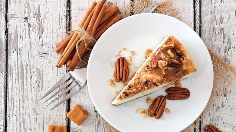 Slice of pecan and caramel topped cheesecake