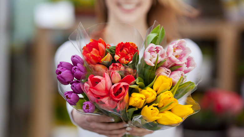 woman offering bouquets of flowers