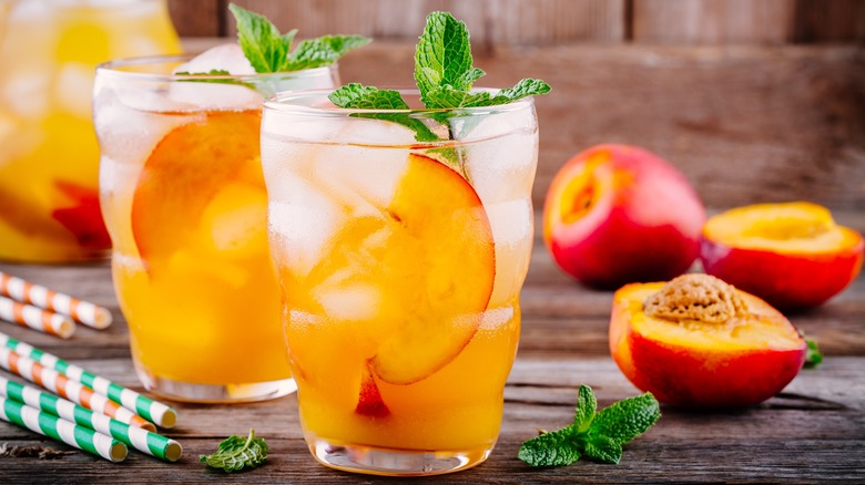 Glasses of cold peach beverages on table