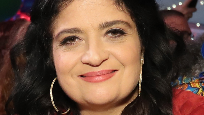 Alex Guarnaschelli wearing a red jacket and smiling