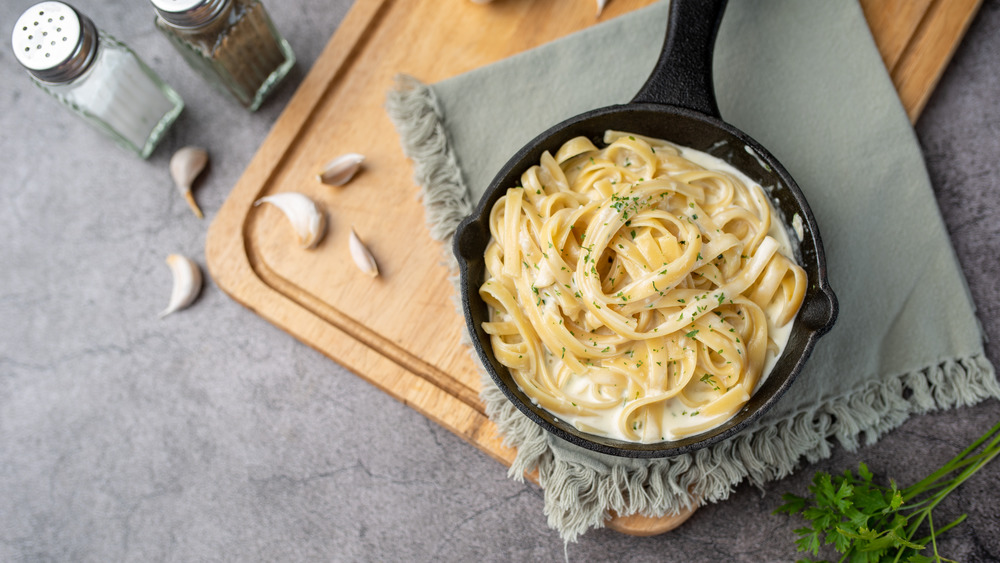 Pasta Alfredo in cast iron skillet on gray cloth and wood cutting board