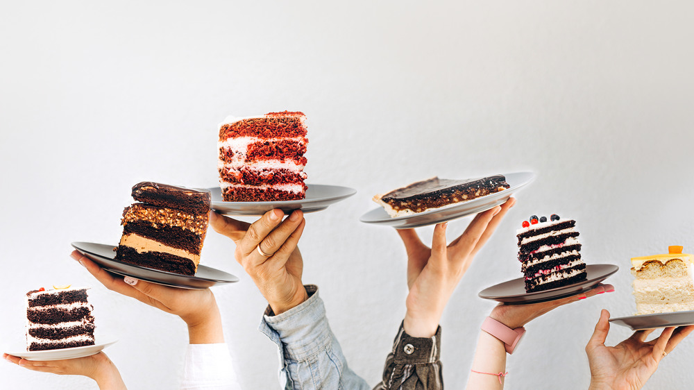 Hands holding different cake slices