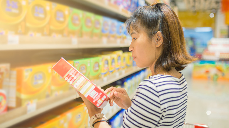 Woman reading food label in grocery aisle