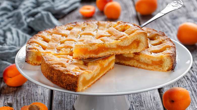 An apricot pie on a cake stand with apricots around it