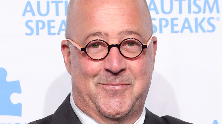 Andrew Zimmern in round glasses
