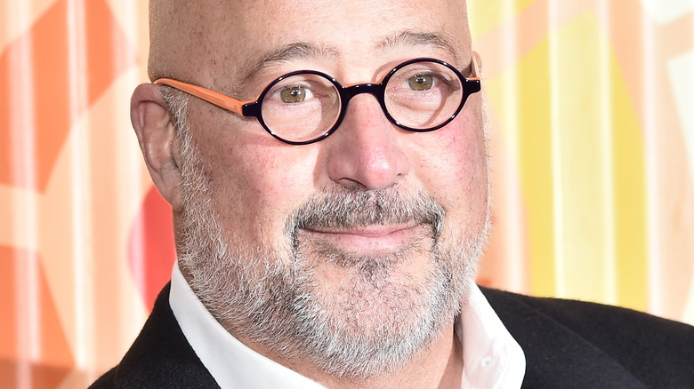 Andrew Zimmern wearing a black suit, white shirt and glasses