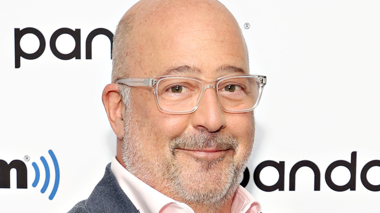 Andrew Zimmern in glasses and pink shirt