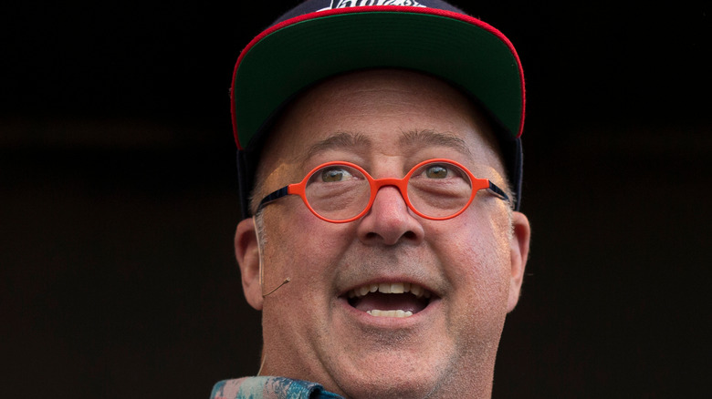 Andrew Zimmern with his head turned in a baseball hat