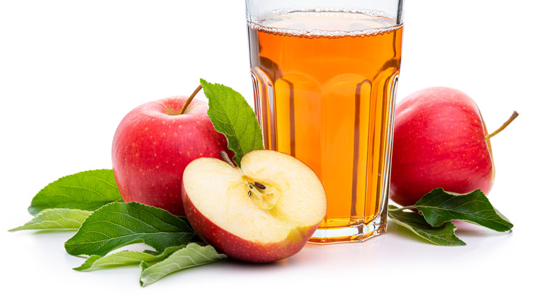 A glass of apple juice surrounded by apple halves.