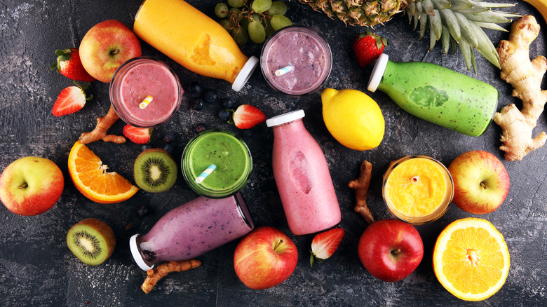 Top view of smoothies in bottles next to fruit