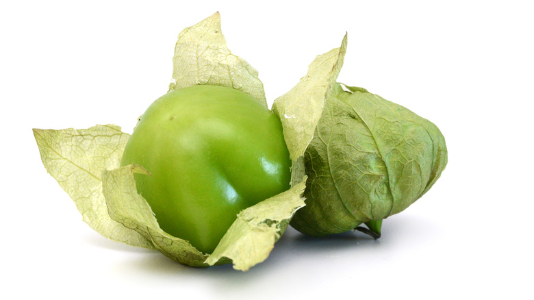 two tomatillos, one unwrapped