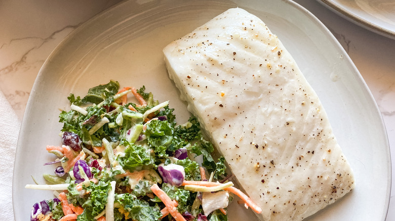 A Baked Halibut Filet on a plate with a salad