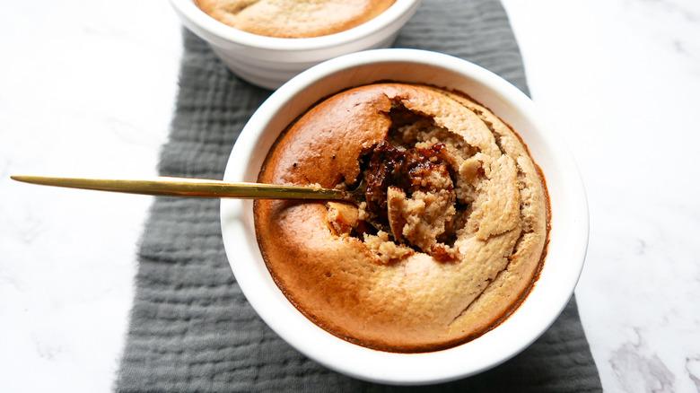Baked oatmeal in ramekin with spoon breaking top