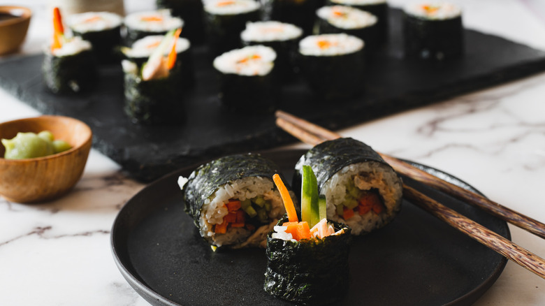 three sushi pieces on a plate with chopsticks
