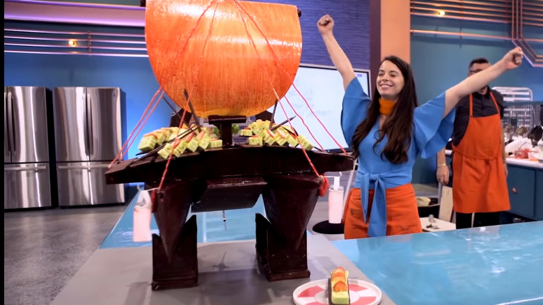 Baking Impossible contestant raising arms