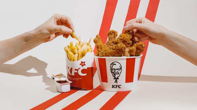 hands hold KFC fried chicken