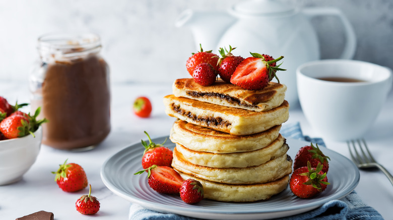 stack of Nutella stuffed pancakes with strawberries